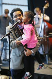 "Darius Ajai Frasure held 5-year-old Siedah Yvonne Frasure up to the mike as she finished his poem ""Love"" at the Ideas Stage on Saturday.( Nathan Hunsinger  -  Staff Photographer )"