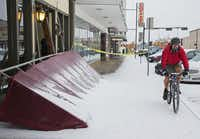 Alex Croy of Denton rode his bike past the fallen awning at La Di Da boutique on Locust Street in Denton following an overnight ice storm.