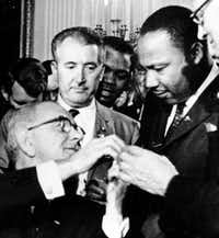 President Lyndon B. Johnson reached to shake hands with the Rev. Martin Luther King Jr. at the signing of the Civil Rights Act in 1964.( File  -  The Associated Press )