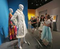 """Haley Schultheis (center) and Kelle Knight (right) got a look at some of Oscar de la Renta's famous fashions at Thursday's preview. Laura Bush said a first lady must look """"appropriate"""" at all times, """"lovely but not too flamboyant.""""Michael Ainsworth  -  Staff Photographer"""