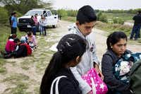 U.S. Border Patrol  agents detain young migrants from Honduras and Guatemala near the Anzalduas Dam at the Mexico-U.S. border. Mexico has vowed to crack down on migrants passing through it illegally, but little has changed.( Todd Heisler  -  The New York Times )