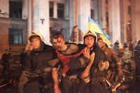 Firefighters evacuated an injured man outside a building that was attacked, where more than 30 people died trying to escape during clashes Friday in Odessa, Ukraine.Sergei Poliakov - The Associated Press