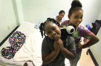 Topaz Griggs watches as daughters Arianna Scott, 6, (left) and Jakayla Asbell, 8, play in the space they share at the Salvation Army shelter in Dallas.