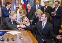 Gov. Greg Abbott and Zachariah Moccia, 25, who has Dravet syndrome during a bill signing ceremony to allow for the use of low-THC cannabis oil to treat intractable epilepsy  on Monday, June 1, 2015 at the Texas state capitol in Austin, Texas. (Ashley Landis/The Dallas Morning News)