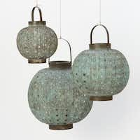Global punch. Line a walkway or pool, or create a pretty bench-topped vignette with blue punched metal globes. Verdigris Filigree lanterns, $68, $98 and $148 at shopterrain.com.( Terrain.com  - SUPPLIED)