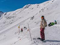 A snowboarder waits at the top of the Bliss Trail.  The ridge-accessed bowl terrain beyond will remain closed until ski patrollers can mitigate the day's avalanche hazards.