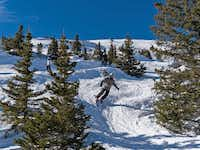 Skiers descend the lower reaches of the Elysian Fields.  Besides blue groomers and double-black plunges, Peak 6 offers acres of intermediate-grade powder and bump terrain.