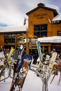 Skis and snowboards stand in racks outside Grand Targhee's Rendezvous Lodge. Built of lumber and logs, Targhee's base area resembles a modernized version of a John Wayne movie set.