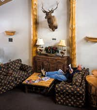 A guest relaxes with a book at Targhee's Teewinot Lodge. The resort offers fewer than 100 rooms, most of which resemble comfortable replicas of quarters reminiscent of a Leave it to Beaver-era motel.