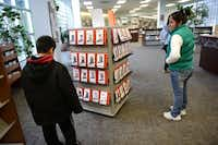 Balda Aguilar and her son Jesus Aguilar, 9, look at a rack of stories on individual mp3 players at the Mesquite Main Library.( ROSE BACA/neighborsgo staff photographer )