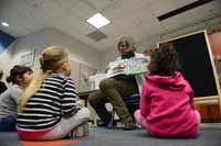 Librarian Betsy Merrill reads to children during Family Storytime at William T. Cozby Public Library.(ROSE BACA)