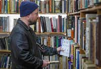 Oak Cliff resident Tim Kerlin peruses the shelves. Lucky Dog Books' space has been leased to Common Desk, a Deep Ellum-based company that rents work areas to small businesses.( Jim Tuttle  -  Staff Photographer )