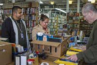 "Lucky Dog Books employee Mark Griffin rings up books and National Geographic magazines for customers Roy Gonzalez and Olivia Pintor. Sales picked up in the last two months, and the owner was encouraged by an uptick in ""younger faces."" But that hasn't been enough to keep the shop open.( Jim Tuttle  -  Staff Photographer )"