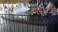 Getting ready to ride: Ellis Holton washed the carousel horses on the midway at Fair Park earlier this week. Love it or hate it, the state fair offers a mosaic of cars, music, rides, animals, hucksters and guilty cuisine.
