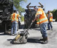 City employee Ricky King worked to patch a pothole Wednesday on Harry Hines Boulevard. The city says Dallas residents ranked streets as their No. 1 priority in a 2014 survey.( Michael Ainsworth  -  Staff Photographer )