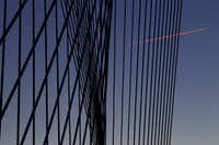 The contrail of a jet appears pink in the light of the setting sun, juxtaposed against the pattern of high-tension cables.