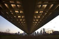 Lights highlight the underside of the bridge roadway decking as seen from inside the levees west of the Trinity River channel.
