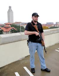 Gun rights activist Michael Short holds a gun as he prepares for a march near the University of Texas, Saturday, Dec. 12, 2015, in Austin, Texas. The group held a mock mass shooting near the campus to remind people a shooter can strike anywhere at any time. (AP Photo/Eric Gay)