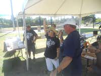 Suzan Mayberry cheers as Robert Waters, a winning competitor in the 2012 annual Steve Mayberry Memorial Cookoff, announces his decision to donate his prize money to Fight Colorectal Cancer, the event's benefit charity. This year's event will be Sept. 6 and 7 in Carrollton.
