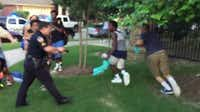 Screenshot from video shows officer pointing gun at two unarmed black teenagers.