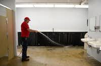 Jones sprays down the men's restroom. As part of the renovations, the troughs will be removed and replaced with stalls that comply with the Americans with Disabilities Act.(Rose Baca - neighborsgo staff photographer)