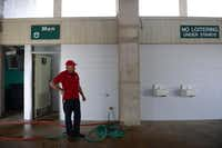 Jones pauses after spraying down the men's restroom in the stadium.(Rose Baca - neighborsgo staff photographer)