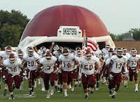 The Mesquite Skeeters run from the team's inflatable helmet prior a game against Arlington Bowie.