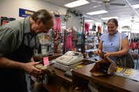 Amy Farrell pays Kenneth Burks for a shoe repair at Messina Shoe Repair in Farmers Branch. Kenneth Burks and his wife Nancy Burks have owned and operated the shop since 1964.Rose Baca  -  neighborsgo staff photographer