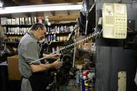Kenneth Burks repairs a shoe and answers a phone call in the back room of his shop, Messina Shoe Repair, in Farmers Branch. Kenneth Burks and his wife, Nancy Burks, have owned and operated the shop since 1964.Rose Baca  -  neighborsgo staff photographer