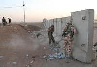 Kurdish fighters took cover during airstrikes by U.S. forces targeting Islamic State militants near the Khazer checkpoint outside the city of Irbil in northern Iraq on Friday. The extremist Islamic State group controls large areas of Syria and Iraq.Khalid Mohammed  -  The Associated Press