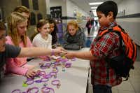 Fourth-grader Jordan Jenkins buys a bracelet from fifth-grade students.( ROSE BACA/neighborsgo staff photographer )