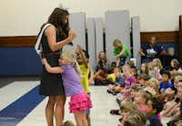 Kindergartener Ryan Adams hugs Miss Texas Monique Evans during an assembly at Saigling Elementary School. Originally Miss Park Cities, Evans, who made headlines for her ballet-style first pitch at the Texas Rangers game Aug. 15, will compete for the Miss America crown Sept. 14.( Photo by Rose Baca  - neighborsgo staff photographer)