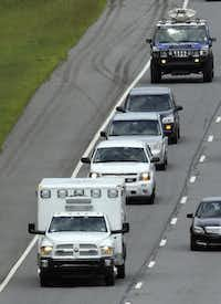 An ambulance left Dobbins Air Reserve Base  near Interstate 75 on Saturday in Marietta, Ga. Only a few cars were in the convoy, and the ambulance drove without lights or sirens.John Bazemore - AP