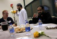 Imam Zia ul Haque Sheikh (center), at a ritual breaking of a Ramadan fast, explains how compassion for the poor can be gained by fasting.