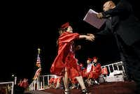Jocelyn Rodriguez walks the stage to receive her diploma during a graduation ceremony at Roma High School. Jocelyn is planning to move to Arizona and begin her college coursework online.