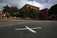 "An ""X"" painted unofficially on Elm Street is intended to mark where President John F. Kennedy was struck by an assassin's bullet while riding in a motorcade through Dealey Plaza on Nov. 22, 1963."