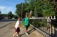 From left: Elliot Espinoza, 9, Armando Torres, 11, and Antonio Gonzalez, 11, play a version of volleyball in Oak Cliff's Exeter Wilhurt neighborhood.