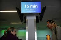 """Video boards along the """"Next Level""""   security checkpoint keep travelers apprised of how long it will take to make it to the TSA inspection at D/FW Airport."""