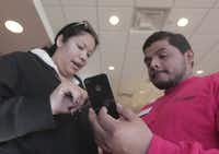 Customer Abigail Rodriguez, left , receives help from Verizon employee Josue Zuniga on setting up her iPhone at the south Arlington Verizon Wireless Store on Thursday.