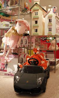 The Neiman Marcus children's department includes unique gifts such as a Lamborghini battery-operated kid's-size black convertible for $395 and wooden doll houses priced at $250 and $350.