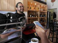 Adrian Reynoso at The Alcove in Dallas serves free coffee to Marty Martinez, who counts on smartphone deals to keep him caffeinated and fed. Martinez, 25, recently launched a digital marketing business and has reined in his spending.( Ron Baselice  -  Staff Photographer )