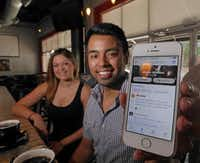 Stephanie Campos (left) and Marty Martinez used the Foursquare app on Martinez's smartphone to receive free coffee at The Alcove in Dallas. He estimates he saves $50 to $60 a week on deals at local businesses.( Ron Baselice  -  Staff Photographer )