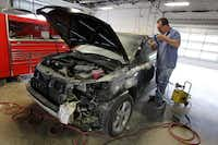 Rafael Trejo, a technician at the Service King in Lewisville, works on a hail-damaged car.