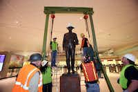 Workers remove protective material from the One Riot, One Ranger statue at Love Field after reinstallation recently in the main lobby. Southwest is set to move next month into a new concourse to replace all existing gates at the 1958-era airport.