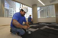 Miguel Zarate (front) and Alexander Benites put down new carpet in an office to be occupied by HKS.
