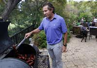 Danny Kearns, Executive Vice President of Scott+Reid General Contractors, Inc. checks on the sausage during a production meeting at Brad Reid's home.