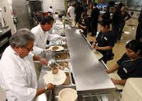 Ty Thoren, left, and Rick Ricci serve lunch to fellow employees at the Gaylord Texan Resort Convention Center.