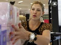 Courtney Watson lines up perfume at the Belk store in Galleria Dallas. The retailer has 14 smaller stores in Texas, including Flower Mound, Fort Worth, McKinney and Rockwall.(Vernon Bryant - Staff Photographer)