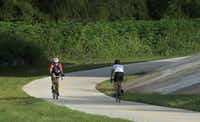 TI electrical design engineer Dave Parks bikes to work from his home in Dallas, Texas on Friday, June 21, 2013. Mr. Parks is shown here on a section of the White Rock Creek Trail as it passes under the DART Rail line. (Brad Loper/The Dallas Morning News)