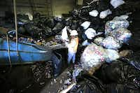 Gilbert Chavez empties trash bags of cans for recycling at Jacobs Iron and Metal. The industry is working with law enforcement to stop unscrupulous scrapyards from buying stolen metals.David Woo  -  Staff Photographer